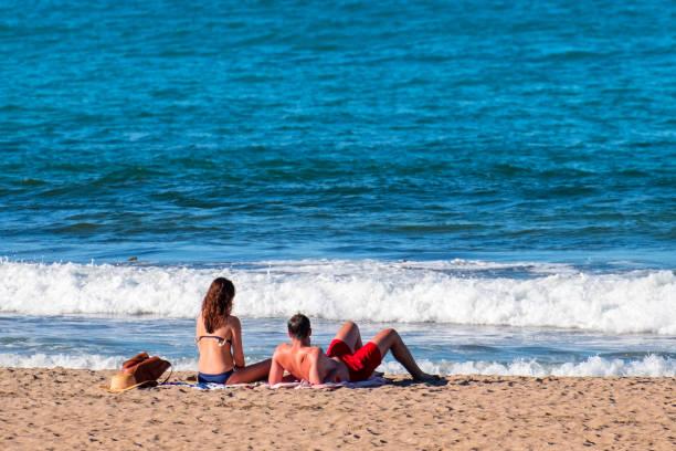 Neuseeland, Coromandel-Ein Paar genießt die Sonne und ein Meer am Strand. – Foto