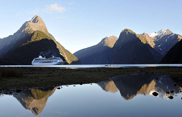 "New Zealand Cruise ""Milford Sound, New Zealand -February, 29th 2012: A cruise ship crosses Milford Sound, New Zealand's most famous tourist destination, on a beautiful still sunny morning."" oceania stock pictures, royalty-free photos & images"
