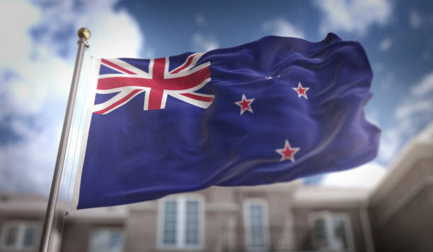 new zealand flag flag 3d rendering on blue sky building background - new zealand flag stock photos and pictures