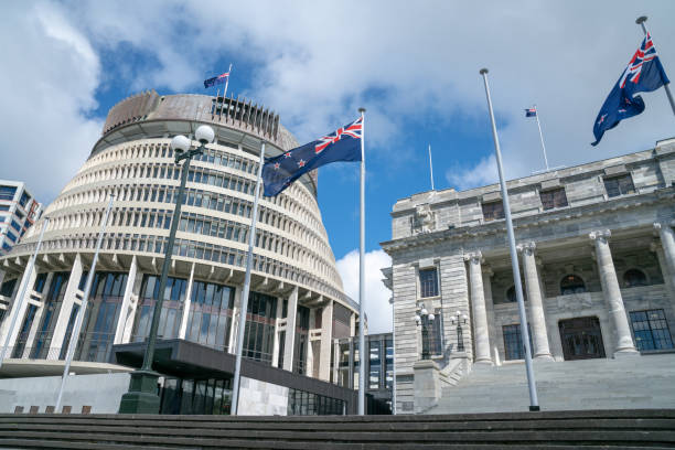New Zealand Government buildings Flags flutter in front New Zealand Government buildings, House neo classical style House of Parliament with Beehive behind. wellington new zealand stock pictures, royalty-free photos & images