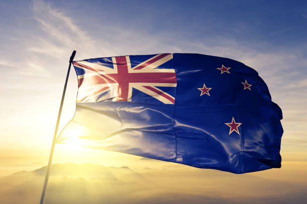 new zealand zealander flag textile cloth fabric waving on the top sunrise mist fog - new zealand flag stock photos and pictures