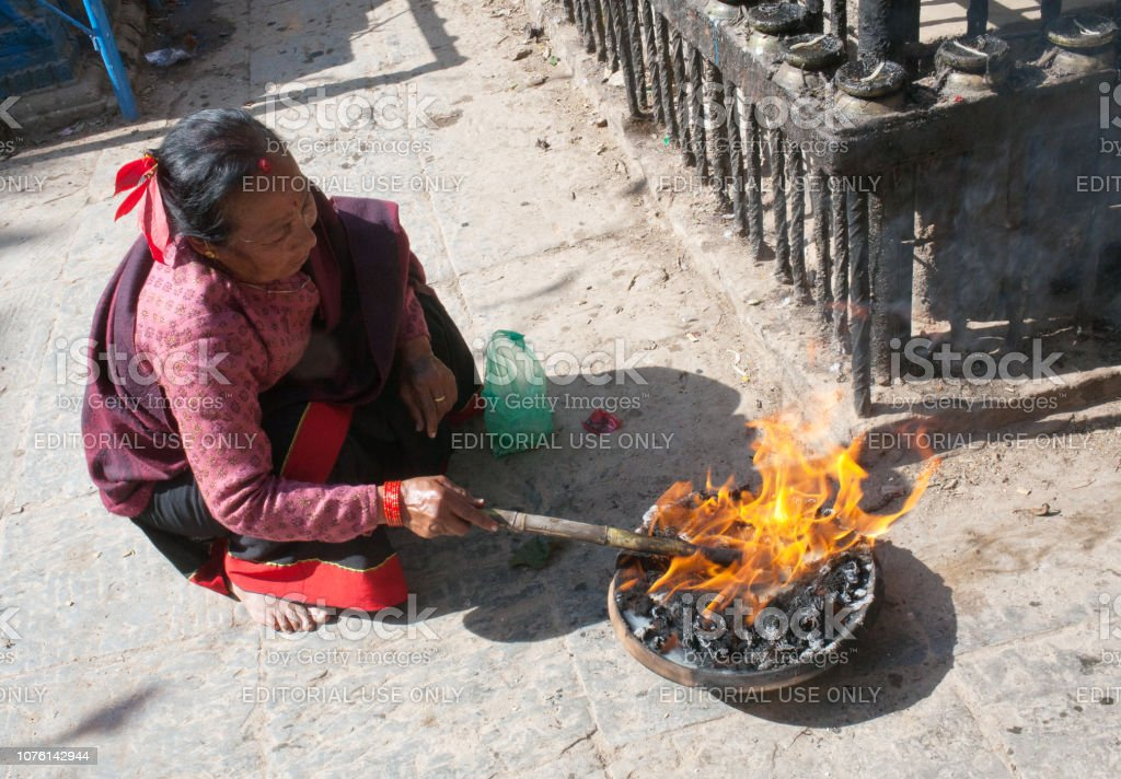 Newari woman kindles the sacrificial fire in hindu temple stock photo