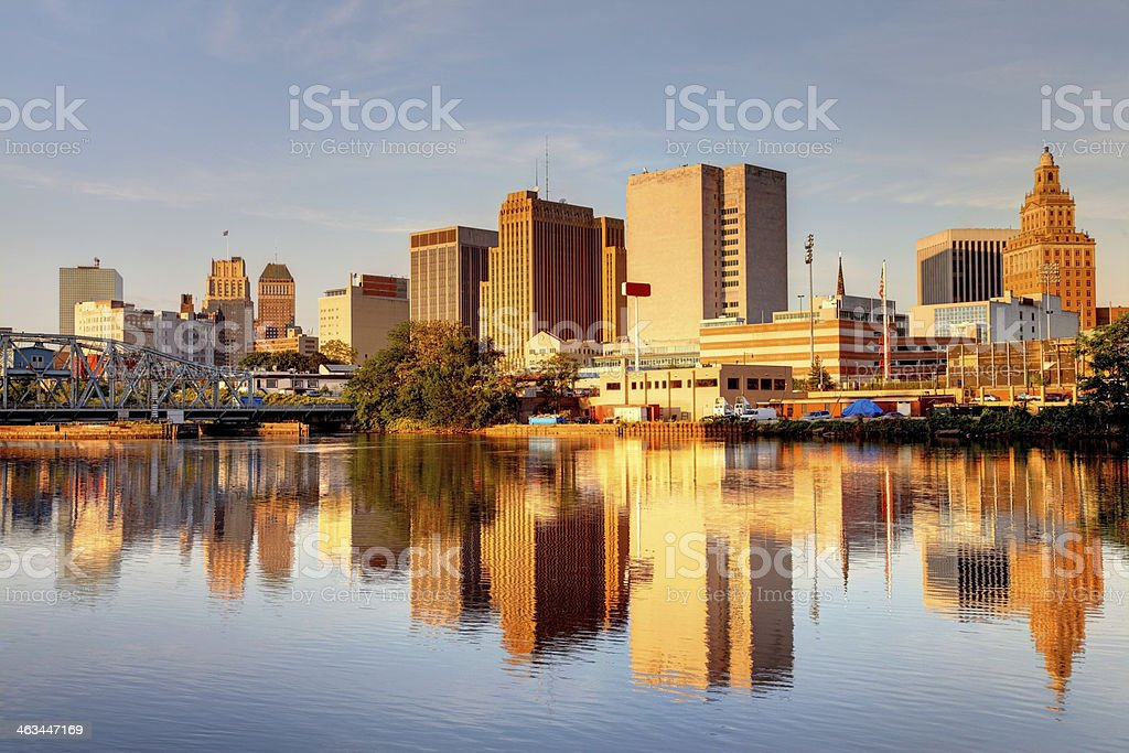 Newark New Jersey Downtown Newark skyline refection on the banks of the Passaic River. Newark is the largest city in New Jersey. Newark is one of largest rail and air hubs in the nation. Newark is known for its glamorous performing arts venues, premium outlet mall, museums, and the argest collection of cherry blossoms. Architecture Stock Photo