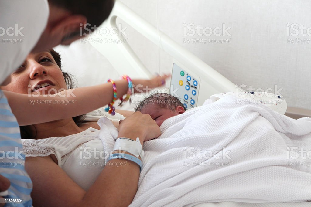 Newborn and family together in hospital room stock photo