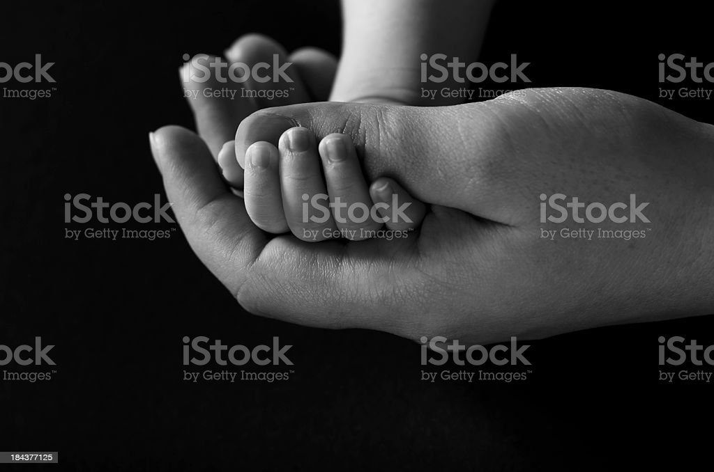 Newborn and mother hands, black background stock photo