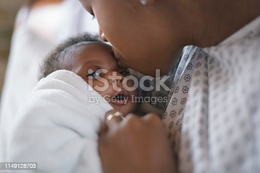 A young mother is kissing her newborn son on the forehead. They are at the hospital. The mother is wearing a hospital gown and the baby is wrapped in a white blanket.