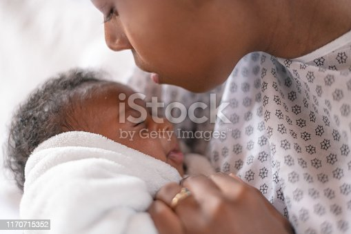 A young mother is kissing her newborn son on the forehead. They are at the hospital. The mother is wearing a hospital gown and the baby is wrapped tightly  in a white blanket.
