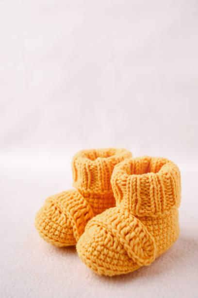 neugeborenen ankündigung. gestrickte babyschuhe auf weißem hintergrund - babyschuh stock-fotos und bilder