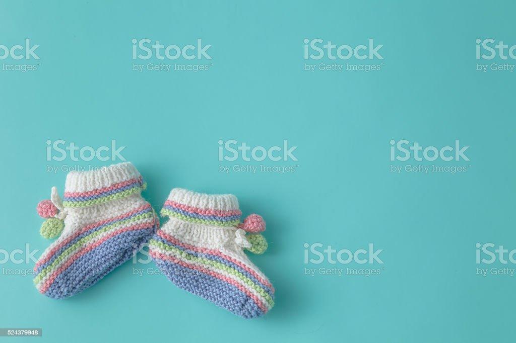 Newborn announcement. knitted baby booties on plain aquamarine b stock photo