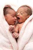 Two hispanic or middle eastern newborn babies posing together