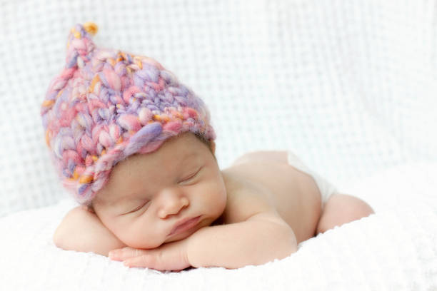 Newborn baby asleep with pink hand knit hat stock photo
