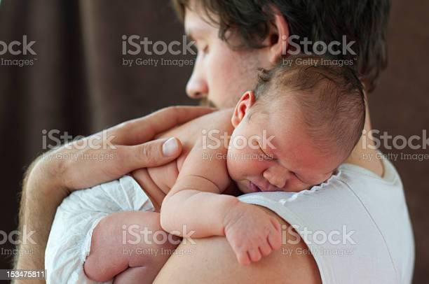A Newborn Baby Being Held By Their Loving Father Stock Photo - Download Image Now