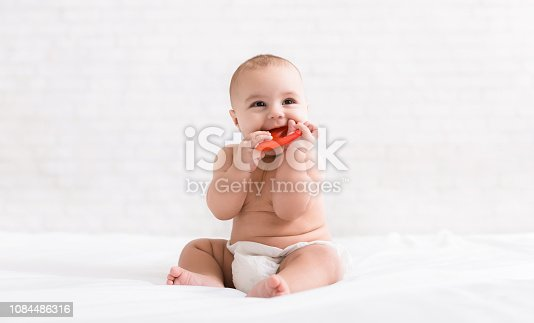 1084486306 istock photo Newborn baby biting red teether in bed 1084486316
