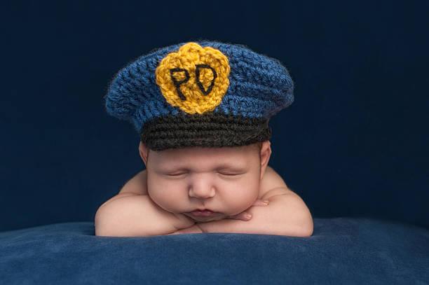 neugeborenes baby trägt einen hut bloy polizei - kindermütze häkeln stock-fotos und bilder
