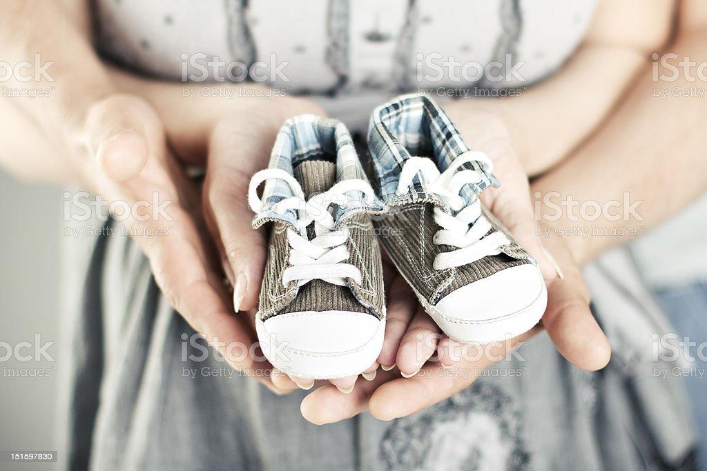 Newborn baby booties in parents hands stock photo