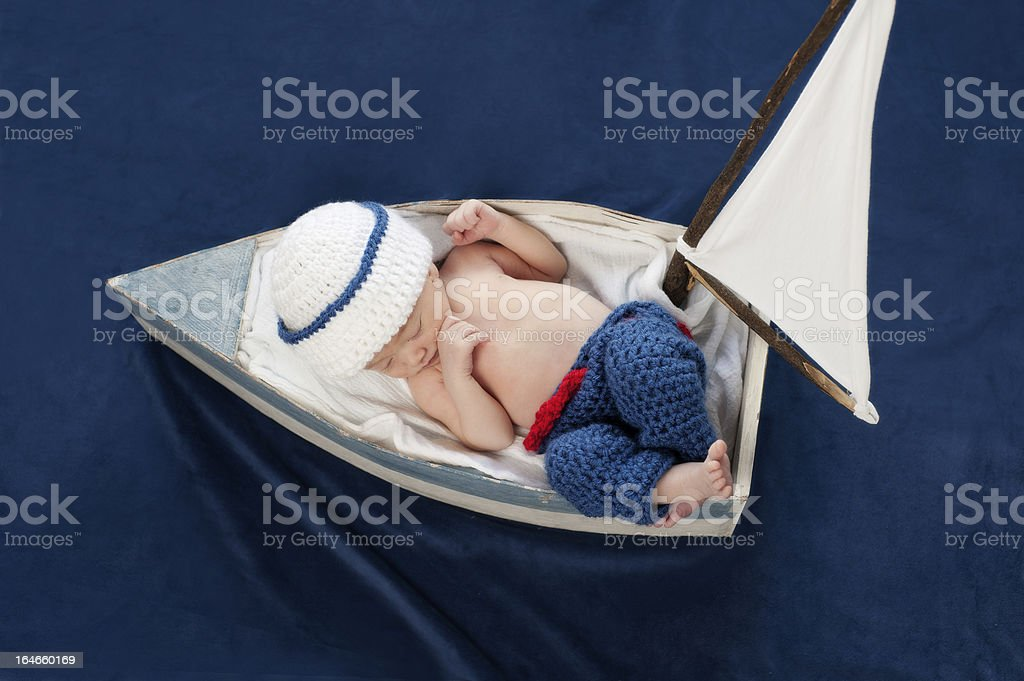 A newborn baby boy asleep in a boat stock photo