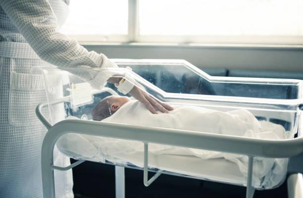 schlafen neugeborene babyjunge bassinet krankenhaus - neugeborene krankenhaus outfits stock-fotos und bilder