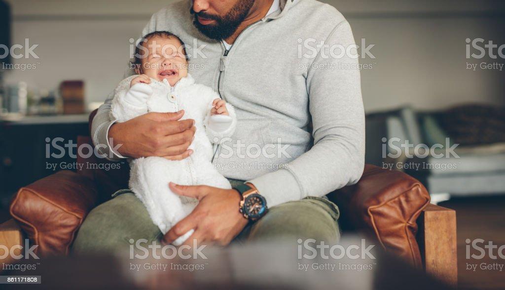 Niño recién nacido llorando en el regazo de su padre - foto de stock