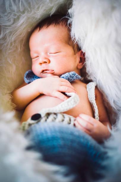 ein neugeborenes baby junge gestrickte krawatte und hose bekleidet - kindermütze häkeln stock-fotos und bilder