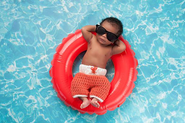 Newborn Baby Boy Floating on a Swim Ring stock photo