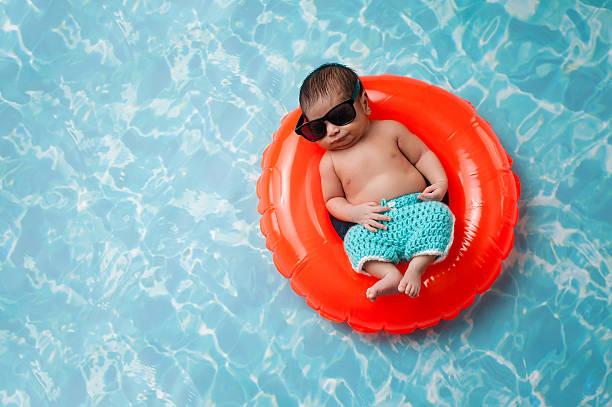 neugeborenes baby jungen, der auf einem runden schlüsselring - traum pools stock-fotos und bilder