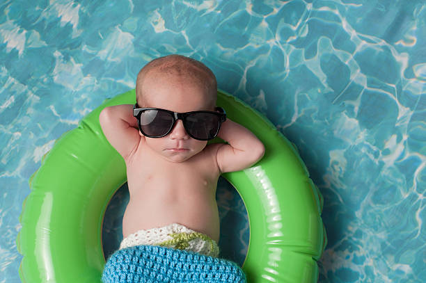Newborn Baby Boy Floating on an Inflatable Swim Ring stock photo