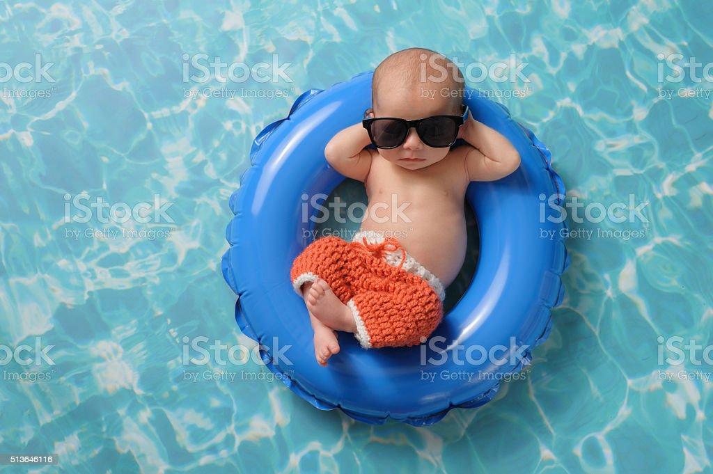 Neonato bambino ragazzo galleggia su un anello gonfiabile nuota
