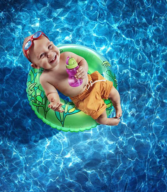 neugeborenes baby boy floating auf einen reifenschlauch - traum pools stock-fotos und bilder