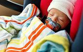 車の座席に生まれたばかりの赤ちゃんの男の子