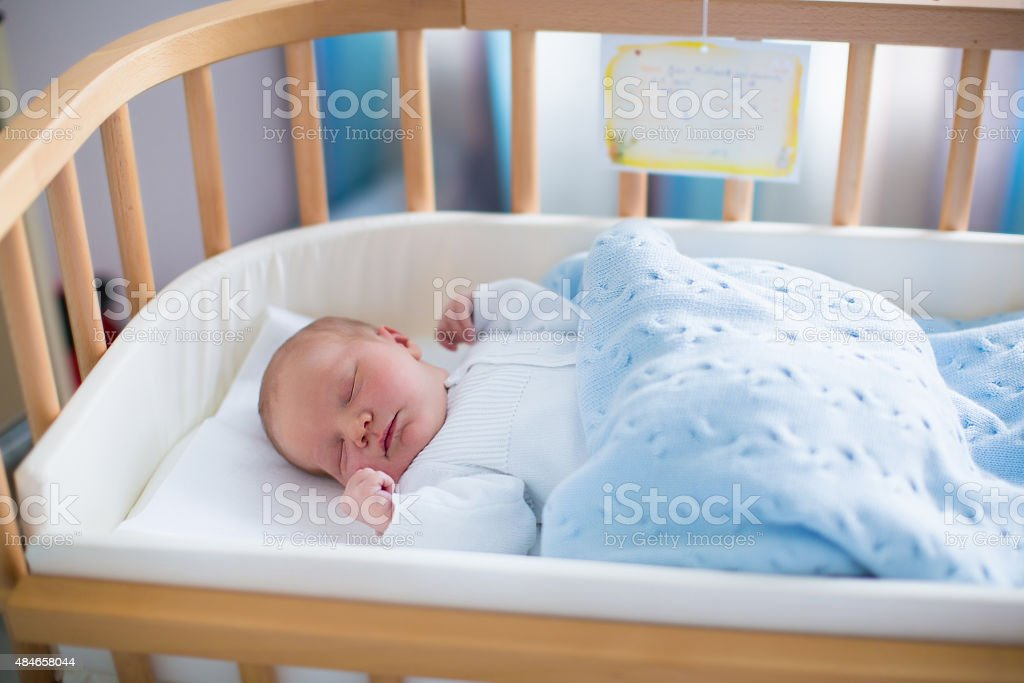 Newborn baby boy in hospital cot stock photo