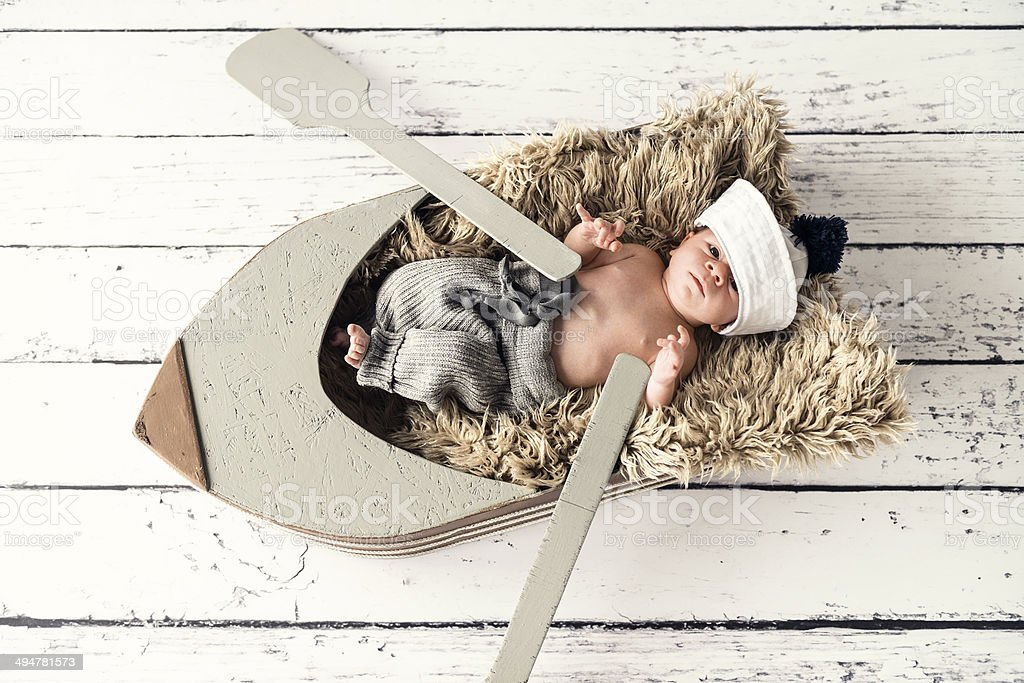 Newborn baby boy is lying on the boat and paddling stock photo