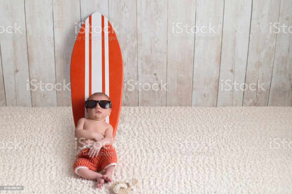 Newborn Baby Boy Leaning on Surfboard stock photo