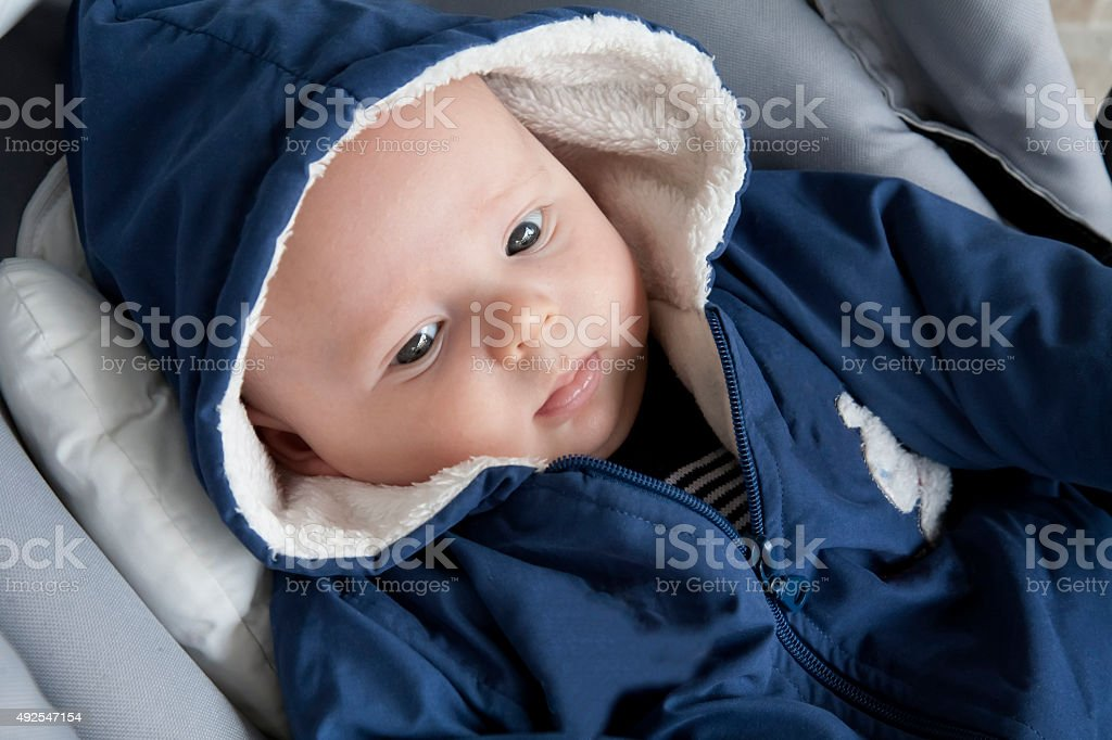 Newborn baby boy lying in a child seat. stock photo