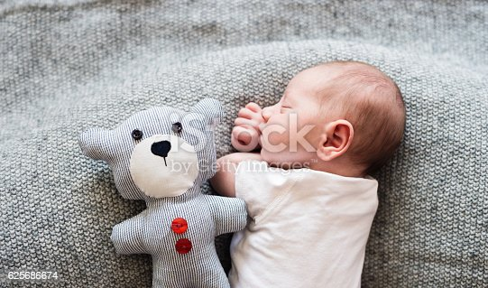istock Newborn baby boy lying on bed with teddy bear, sleeping 625686674