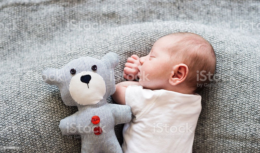 Newborn baby boy lying on bed with teddy bear, sleeping stock photo