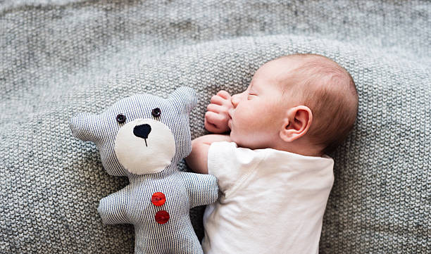 newborn baby boy lying on bed with teddy bear, sleeping - ruhe grau stock-fotos und bilder