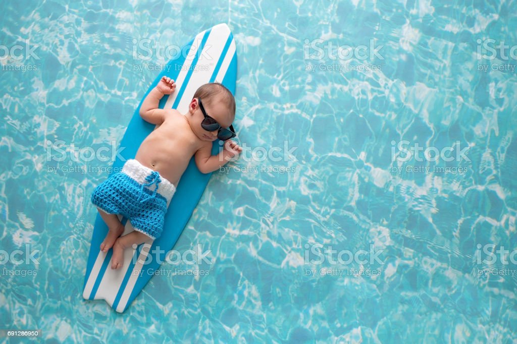 Newborn Baby Boy on Surfboard stock photo