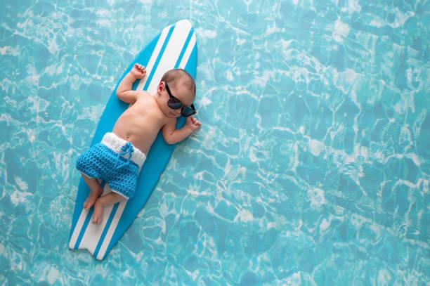 Newborn Baby Boy on Surfboard stock photo