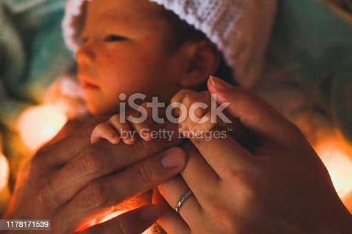 Asian newborn baby boy is wrapping costume and illuminated