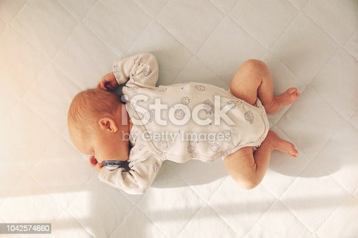 newborn baby boy sleeping in a cot. top view