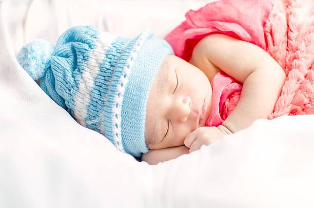Newborn baby boy sleeping in basket stock photo