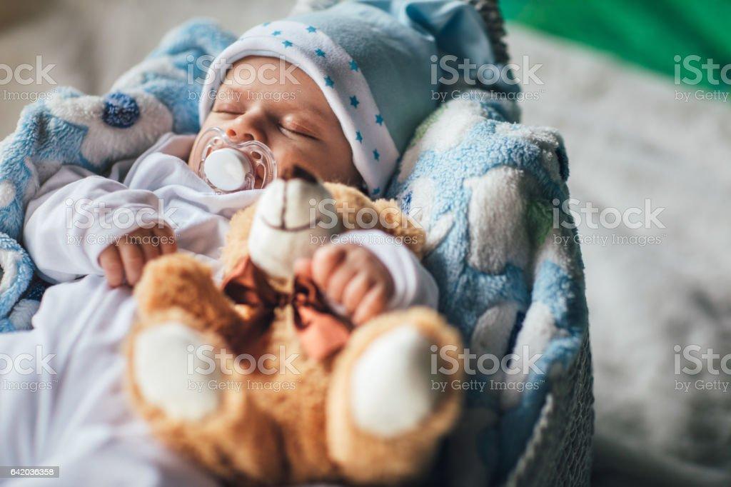 Newborn baby boy sleeping in cozy basket stock photo