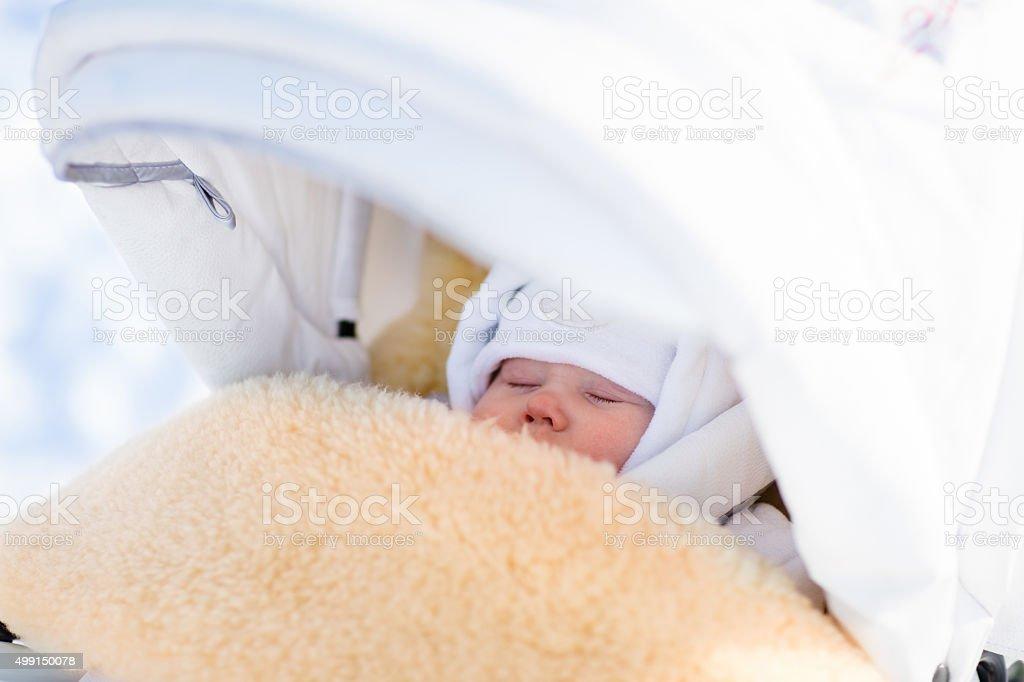 Newborn baby boy sleeping in stroller in winter stock photo