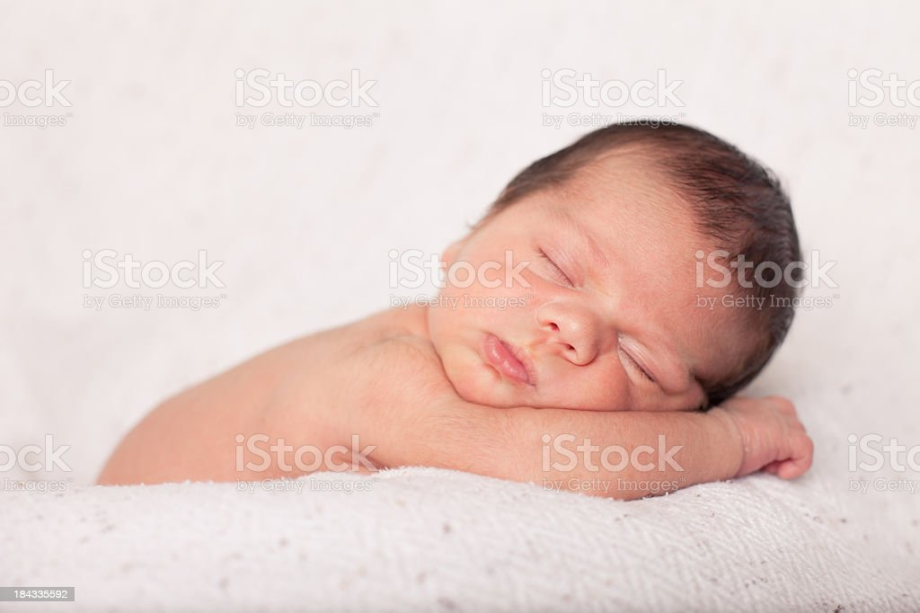 Color photo of a mixed race newborn baby boy sleeping peacefully on a...