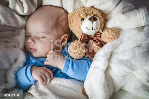 istock Newborn baby boy sleeping together with teddy bear 642035110