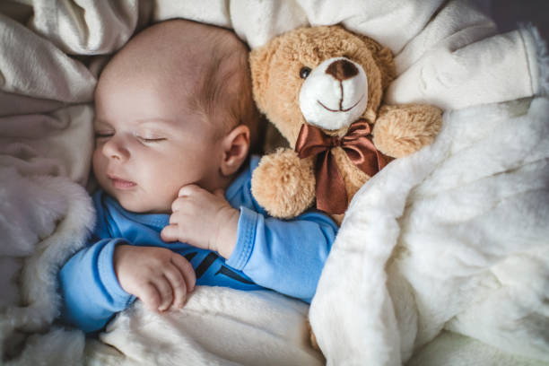 Newborn baby boy sleeping together with teddy bear stock photo
