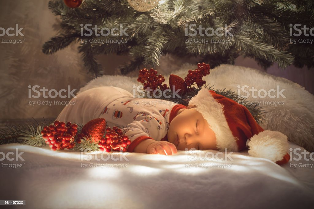 Newborn Christmas Pictures.Newborn Baby Boy Sleeping Under Christmas Tree Near Lot Of Decorations Wearing Santas Hat Stock Photo Download Image Now