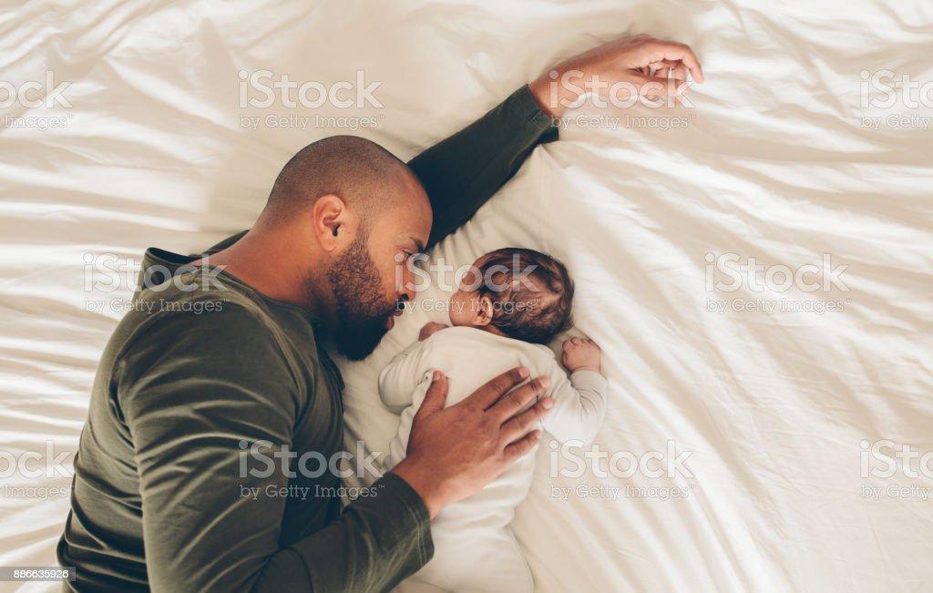 Garçon nouveau-né dort avec son père sur le lit - Photo