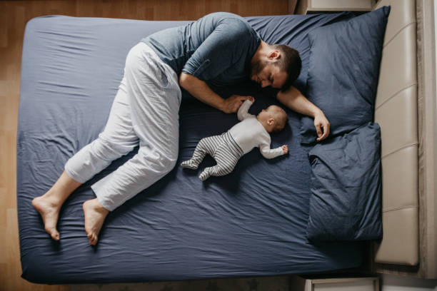 Newborn baby boy sleeping with his father on bed stock photo