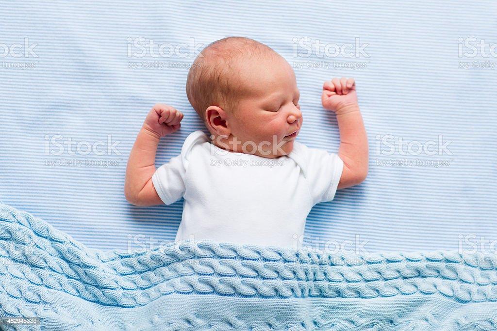 Newborn baby boy under a blue blanket stock photo